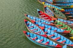 Barcos de madeira velhos verdes amarelos vermelhos azuis na água Barcos de enfileiramento no lago ondas pequenas na superfície da fotografia de stock royalty free