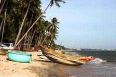 Barcos de madera debajo de las palmeras en la playa tropical Fotografía de archivo