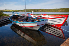 Barcos de madera flotantes del color con las paletas en un lago Imágenes de archivo libres de regalías