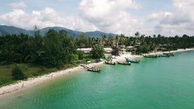 Barcos de mar que se colocan en orilla cercana del estacionamiento en la opinión aérea de las palmeras del fondo almacen de video