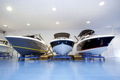 Barcos de motor en salón de muestras o garage foto de archivo