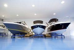 Barcos de motor na sala de exposições ou na garagem Foto de Stock