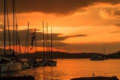 Barcos de navegación en la puesta del sol en la isla de Poros en Grecia fotos de archivo