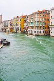 Barcos de navegaci?n de la gente y taxis del agua al lado de edificios venecianos g?ticos en un d?a lluvioso de noviembre en el c imagenes de archivo