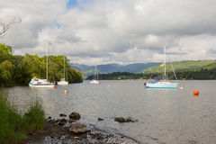 Barcos de navigação em um lago com as montanhas no fundo Fotografia de Stock