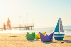 Barcos de papel, barco de madera y gente que camina en la playa Foto de archivo