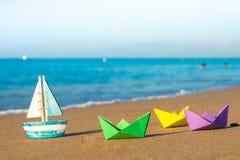 Barcos de papel y barco de madera en la costa Fotografía de archivo libre de regalías