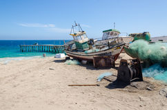 Barcos de pesca abandonados que se descoloran lejos en la playa abandonada en Angola foto de archivo