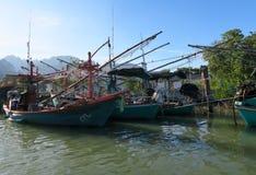 Barcos de pesca de madera tradicionales delante de un pueblo Foto de archivo