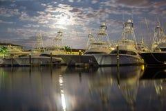 Barcos de pesca debajo de una luna de levantamiento Foto de archivo libre de regalías
