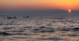 Barcos de pesca em ondas e em por do sol Fotografia de Stock Royalty Free