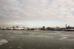 Barcos de pesca em um porto durante o inverno e em um céu azul com água de gelo Fotos de Stock
