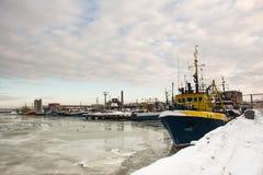 Barcos de pesca em um porto durante o inverno e em um céu azul com água de gelo Imagens de Stock Royalty Free