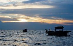 Barcos de pesca en la playa en la puesta del sol Fotografía de archivo