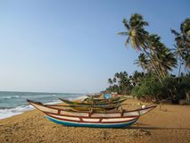 Barcos de pesca en una playa arenosa con las palmeras imagenes de archivo