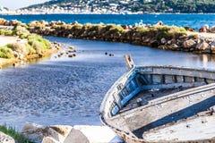 Barcos de pesca envejecidos y abandonados que ponen cerca de un río Foto de archivo
