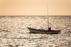 Barcos de pesca flotantes encallado en el puerto en la puesta del sol t del mar fotos de archivo