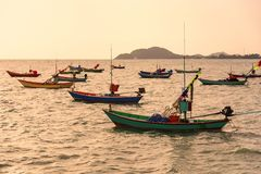 Barcos de pesca flotantes encallado en el puerto en la puesta del sol t del mar imagen de archivo libre de regalías