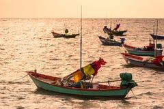 Barcos de pesca flotantes encallado en el puerto en la puesta del sol t del mar foto de archivo