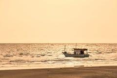 Barcos de pesca flotantes encallado en el puerto en la puesta del sol t del mar imagen de archivo