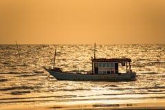 Barcos de pesca flotantes encallado en el puerto en la puesta del sol t del mar imágenes de archivo libres de regalías