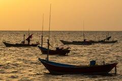 Barcos de pesca flotantes encallado en el puerto en la puesta del sol t del mar fotografía de archivo libre de regalías