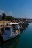 Barcos de pesca mediterrâneos Multi-coloridos ensolarados ancorados na água em Euboea - Nea Artaki, Grécia fotografia de stock