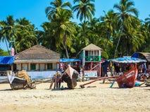Barcos de pesca, palmeras tropicales, casas de planta baja y vida en las calles en la playa de Palolem foto de archivo
