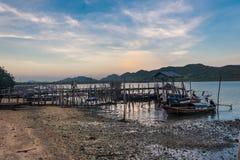 Barcos de pesca parqueados en el embarcadero en un pueblo del pescador con las montañas y el cielo hermosos detrás, sur Tailandia fotos de archivo