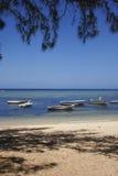 Barcos de pesca pequenos pelo mar azul sob o céu azul na praia Fotografia de Stock
