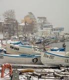 Barcos de pesca pequenos sob a neve em Pomorie, Bulgária Foto de Stock