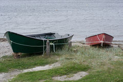 Barcos de pesca vermelhos e verdes amarrados fora com corda Foto de Stock