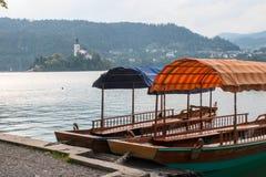 Barcos de Pletna en el lago Bled y la isla sangrada Foto de archivo libre de regalías