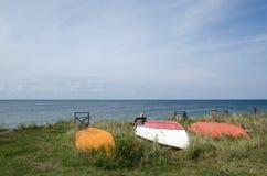 Barcos de rowing encima del lado abajo por la costa Fotos de archivo libres de regalías
