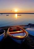 Barcos de Rowing viejos por la puesta del sol de Sea During Imagenes de archivo