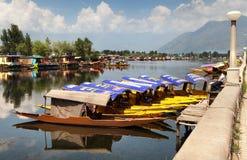 Barcos de Shikara en Dal Lake con las casas flotantes Foto de archivo