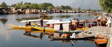 Barcos de Shikara en Dal Lake con las casas flotantes en Srinagar - Shikara es un bote pequeño usado para el transporte adentro Fotografía de archivo