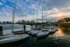 Barcos de vela con horizonte de Boston céntrica en la puesta del sol, en Boston, foto de archivo