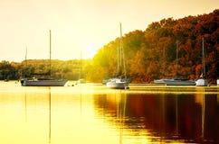 Barcos de vela en el lago en la puesta del sol Foto de archivo