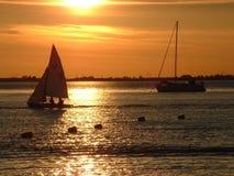 Barcos de vela en la puesta del sol Fotografía de archivo