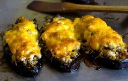Barcos del calabacín de la berenjena rellenos con la carne, el arroz, el tomate y las setas con queso rallado fotos de archivo