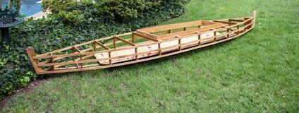 Barcos del edificio - un kajak de madera parcialmente construido se sienta en hierba cerca de una piscina y shubbery con las flor foto de archivo