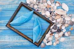 Barcos del papel azul y cáscaras del mar en marco de la foto Imagen de archivo