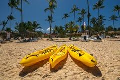 Barcos do caiaque da canoa na praia tropical ensolarada com palmeiras Imagem de Stock