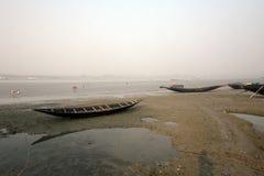 Barcos dos pescadores encalhados na lama na maré baixa na cidade de colocação em latas próxima de Malta do rio, Índia Foto de Stock