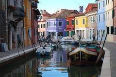 Barcos e casas coloridas em um canal em Burano, Itália foto de stock royalty free