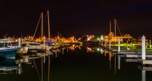 Barcos e docas que refletem na água na noite, em um porto sobre Fotos de Stock Royalty Free