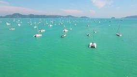 Barcos e iate brancos na água azul clara perto do cais Tiro slowmotion aéreo de HD Phuket, Tailândia vídeos de arquivo