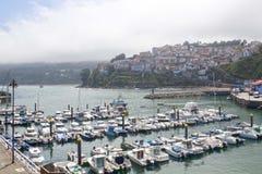 Barcos em um porto em Lastres com a vila atrás, as Astúrias foto de stock