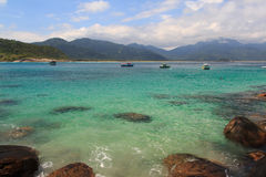 Barcos en el agua transparente de la playa Aventueiro de la isla Ilha grande, el Brasil Fotos de archivo libres de regalías